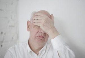 Załamany profesor zakrywa ręką oczy - ktoś źle ubrał się na egzamin?