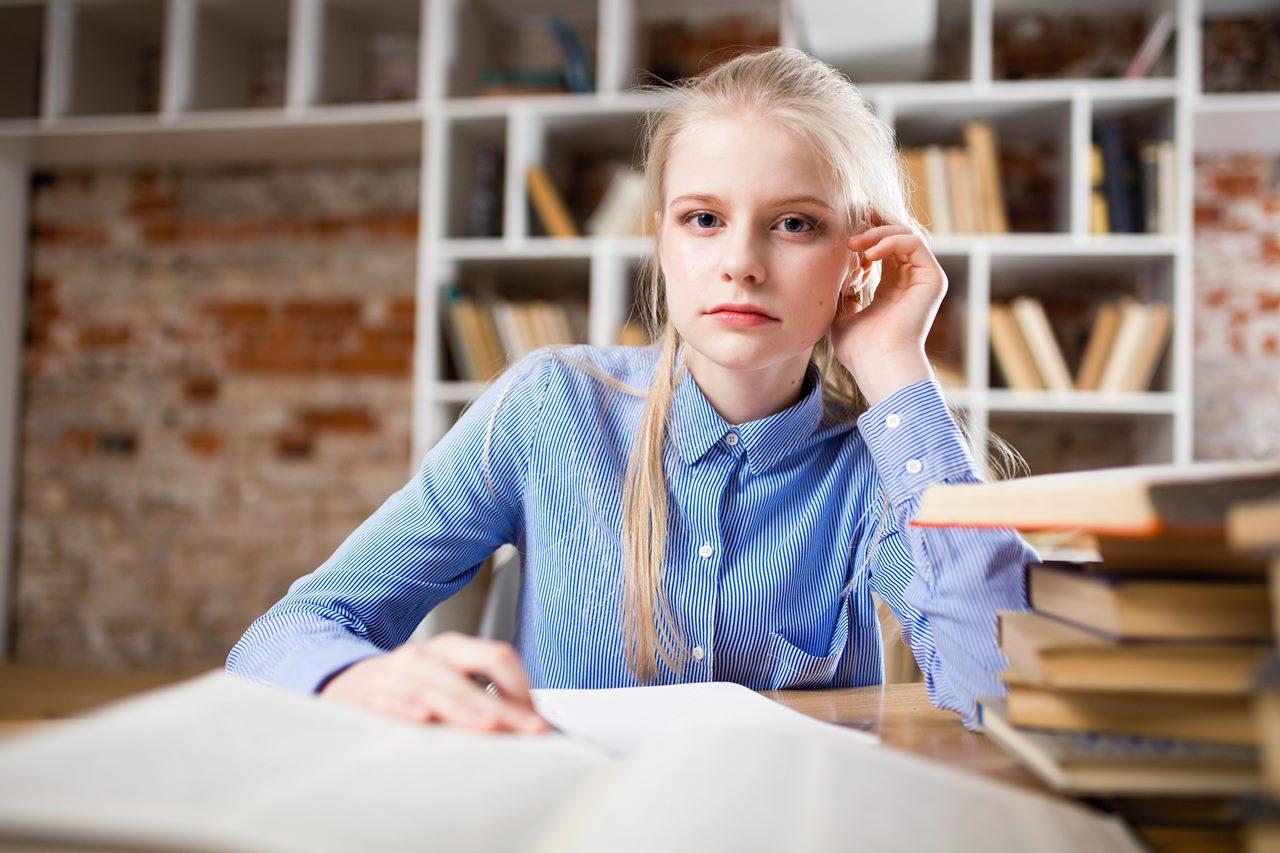 Młoda kobieta uczy się i zastanawia jak ubrać się na egzamin