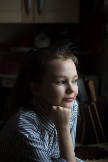 Zamyślona dziewczynka podpiera podbródek piąstką. Jest dużo smaku w tym wyglądzie z klasą