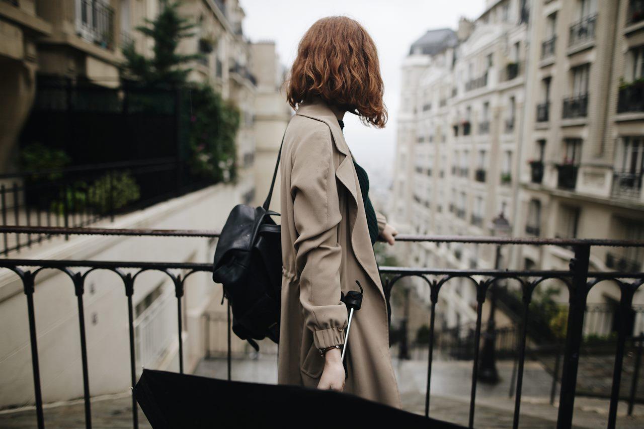 młoda kobieta w trenczu przygląda się, gdzie prowadzi ulica