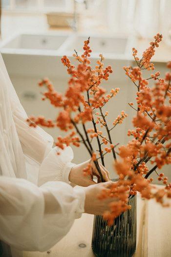 Kobieta układa gałązki obsypane kwiatami w wazonie. Widać tylko ręce w szerokich, przezroczystych rękawach, spięte mankietem z klasą.